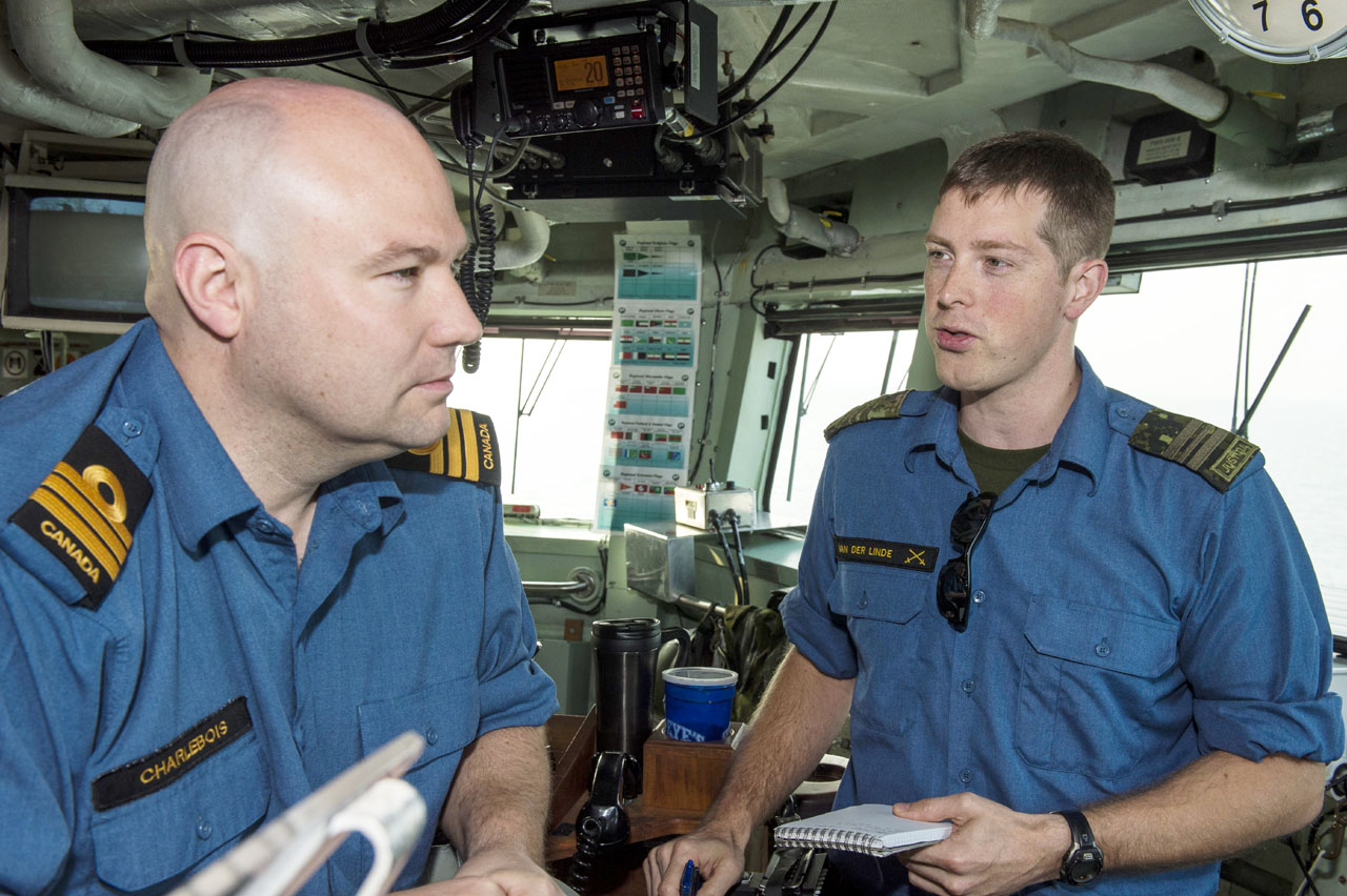 Major Adam van der Linde, right, advises Commander Dan Charlebois, commanding officer of HMCS Regina, on the ship's bridge.