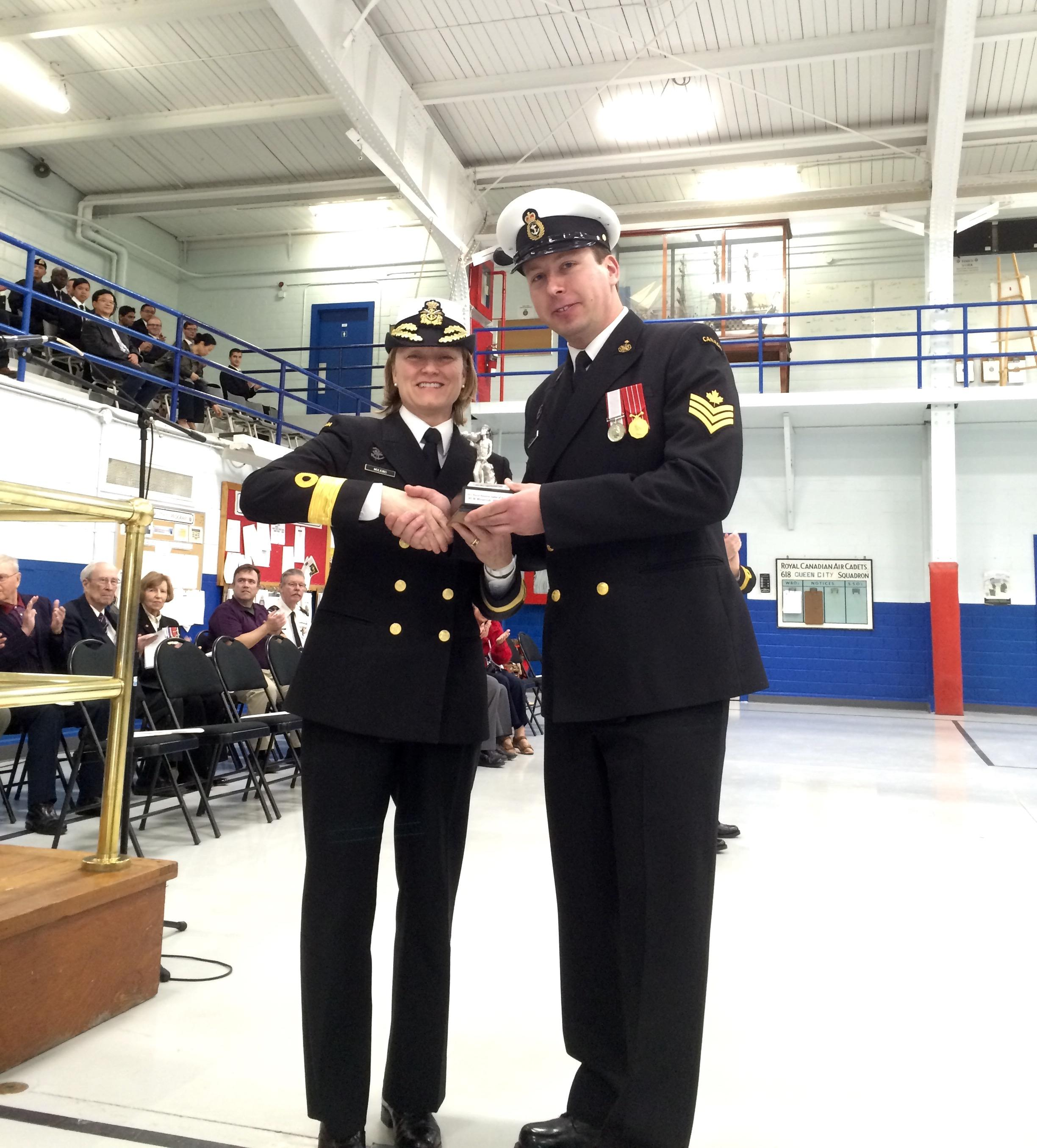 Commodore Marta Mulkins, Commander Naval Reserve, presents Petty Officer 2nd Class Michael Mlynarczyk with a replica of the Naval Reserve Sailor of the Year trophy