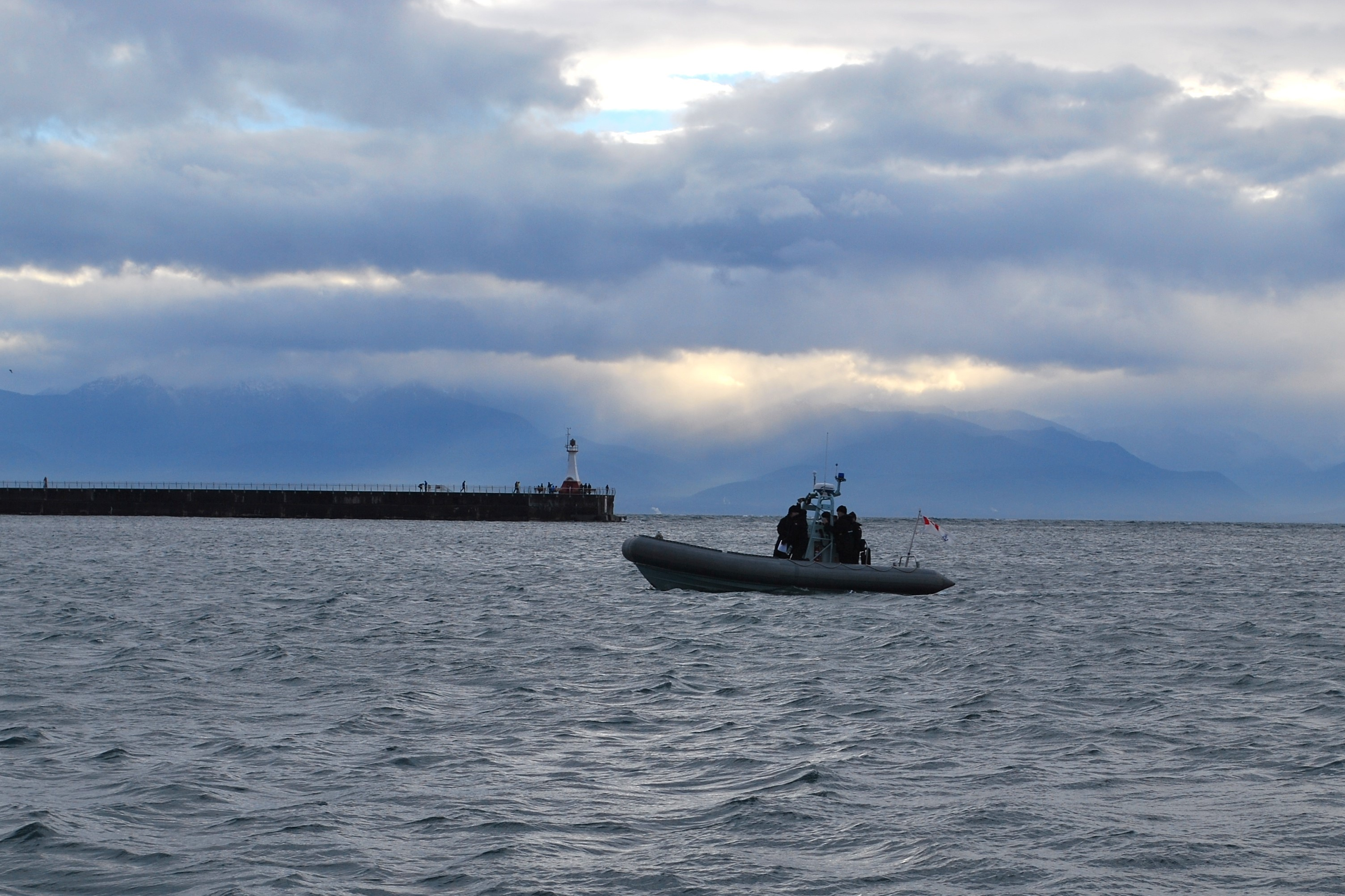 A small boat from HMCS Malahat establishes a security checkpoint near the Ogden Point breakwater at the entrance to Victoria Harbour, on Saturday October 29th, 2016.
