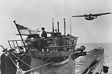 An RCN crew handles the surrendered U-889 off Shelburne, Nova Scotia, as a Royal Canadian Air Force (RCAF) Canso flying boat passes overhead.