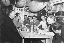 Chief of the Naval Staff, Vice- Admiral Rollo Mainguy, shares a coffee in the seamen's mess of Athabaskan while visiting the ship in Korean waters, February 1953.