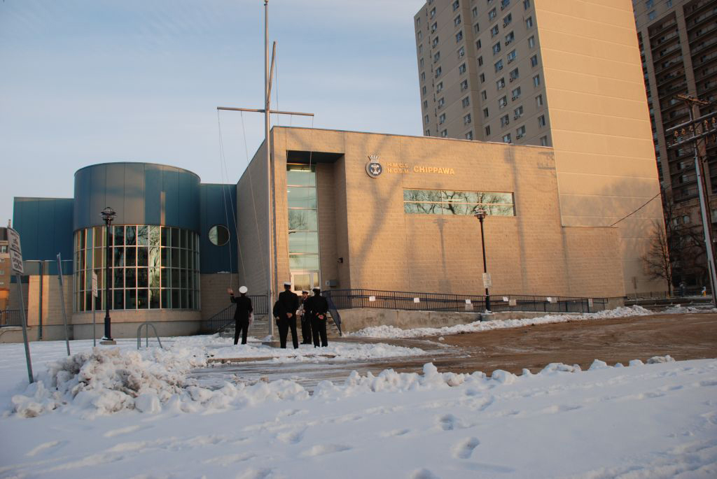 Naval officers stand in front of a building surrounded by snow.