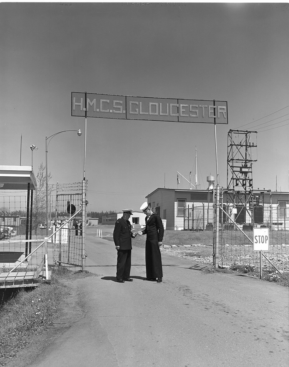 Two naval officers stand under the sign for HMCS Gloucester Naval Radio Station.