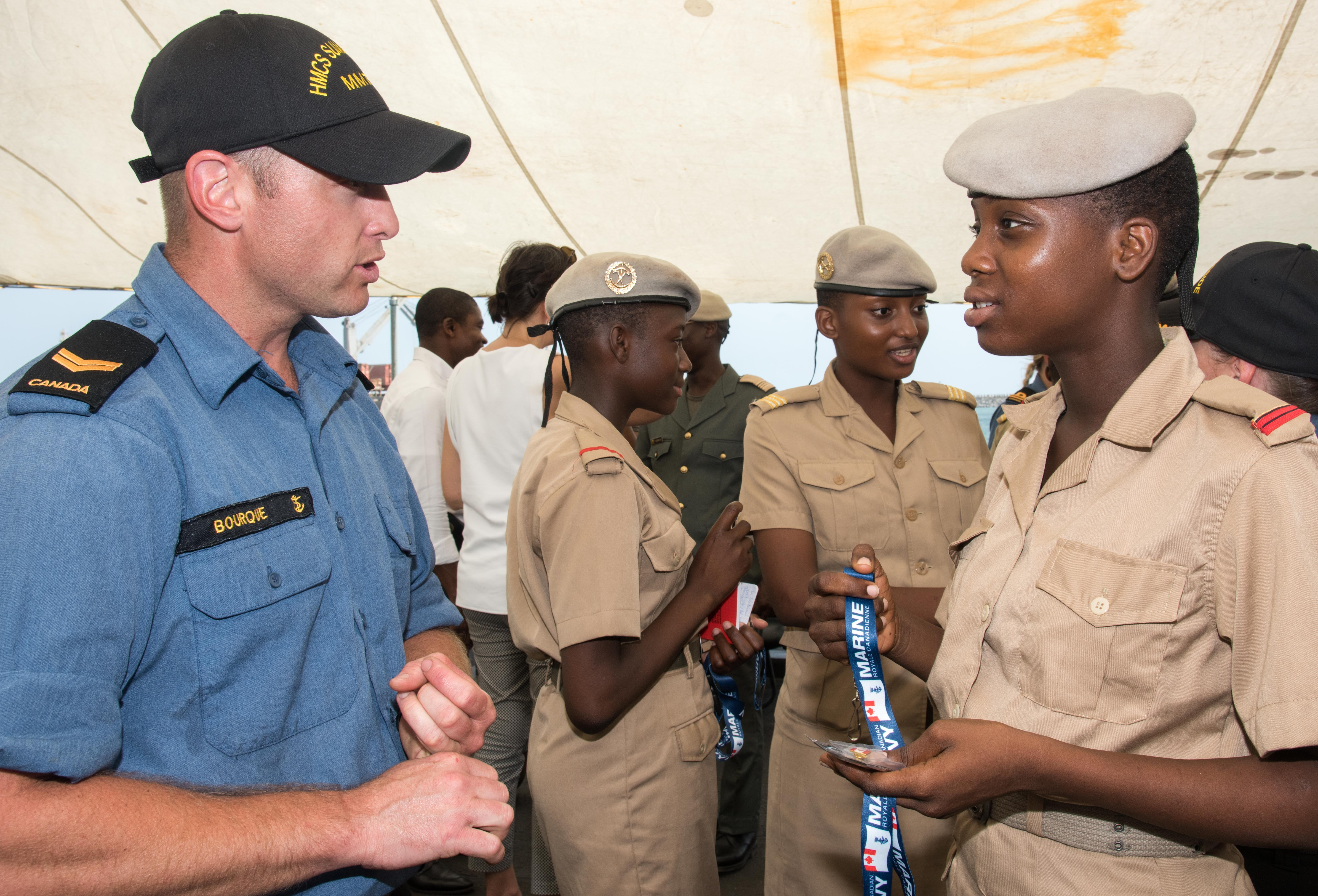 slide - Leading Seaman Robert Bourque talks to visitors aboard HMCS Summerside during a visit to Benin, West Africa.