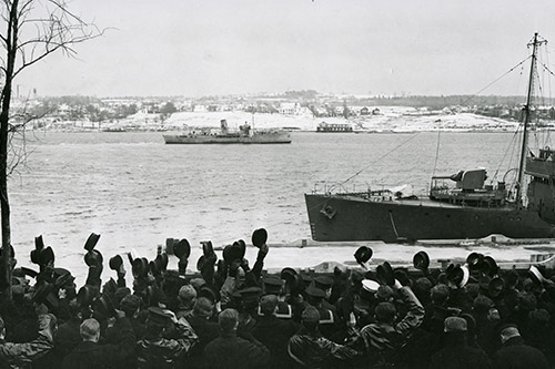 HMCS Windflower proceeding to sea while sailors onshore give them a hearty farewell.