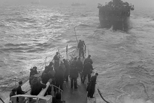 The destroyer HMCS St. Francis, which is escorting a convoy, prepares to take on fuel from a tanker at sea November 7, 1942.