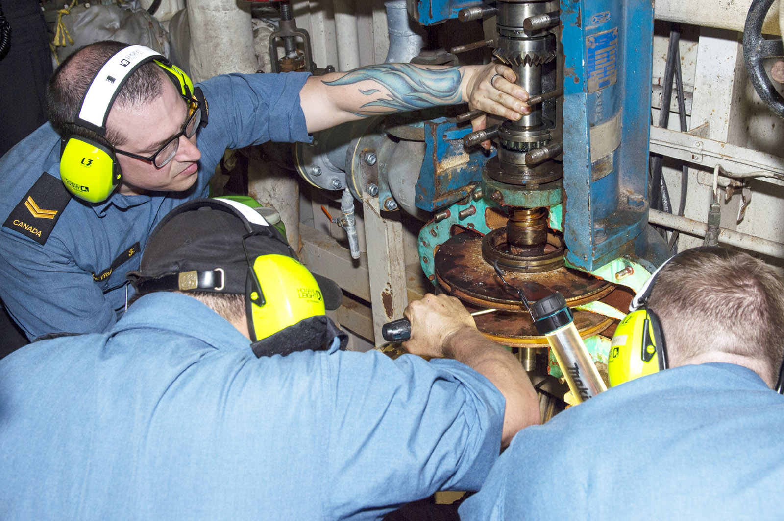 Naval engineers conduct scheduled maintenance on a piece of machinery.