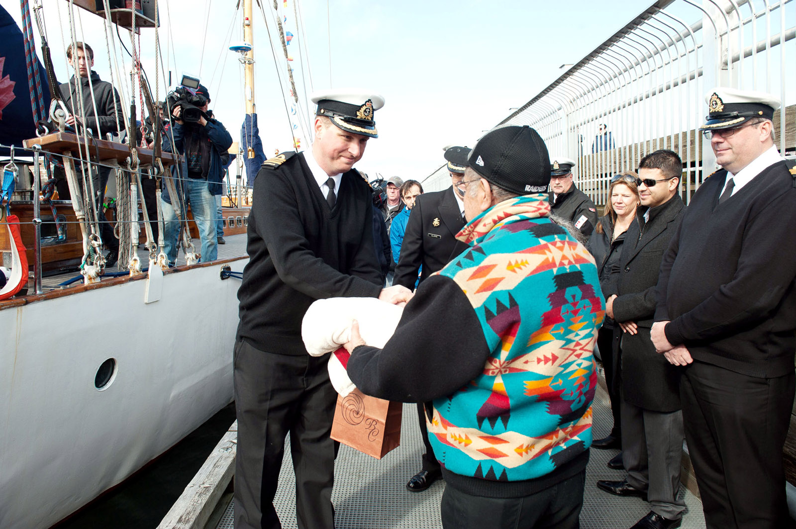 Lieutenant-Commander Michael Wills, commanding officer of HMCS Oriole, thanks Elder Elmer George of the Esquimalt and Songhees Nations for performing a blessing ceremony prior to leaving on a 10,000 nautical mile voyage.