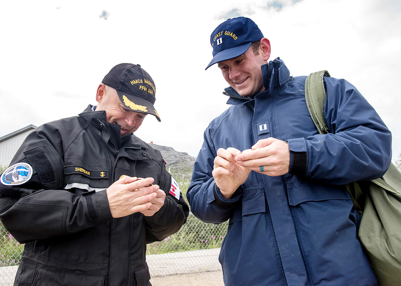 Commander Chris Sherban, left, Commanding Officer of HMCS Montréal, exchanges a coin with a member of the United States Coast Guard in Nain, Labrador.