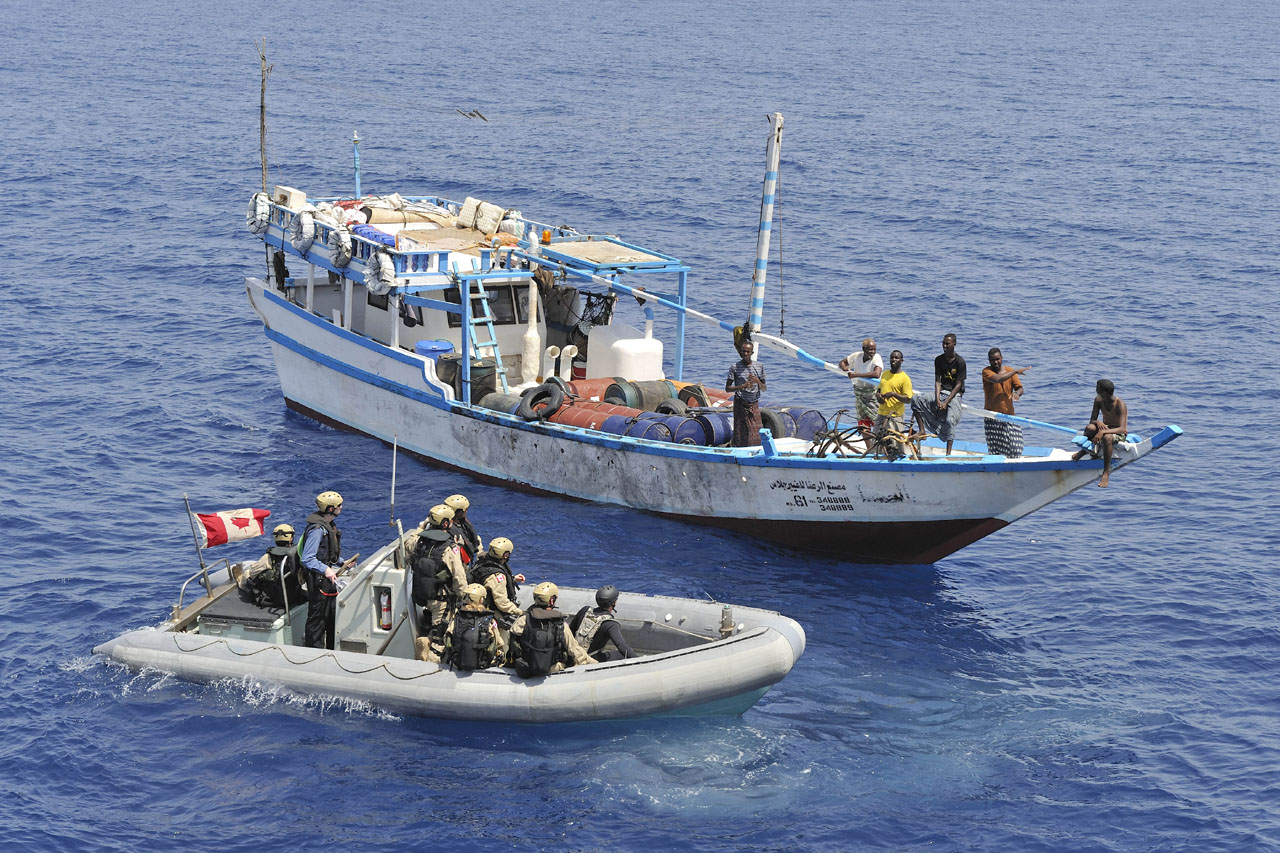 Members of HMCS Regina's naval boarding party come alongside a fishing dhow in the Arabian Sea region.