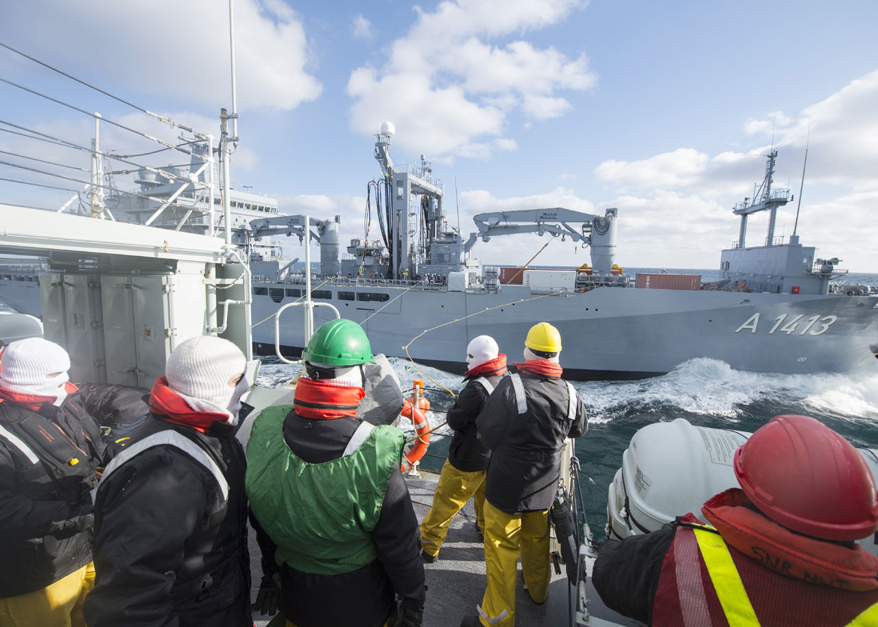 HMCS Iroquois crew members conduct a replenishment-at-sea with Federal German Ship Bonn.