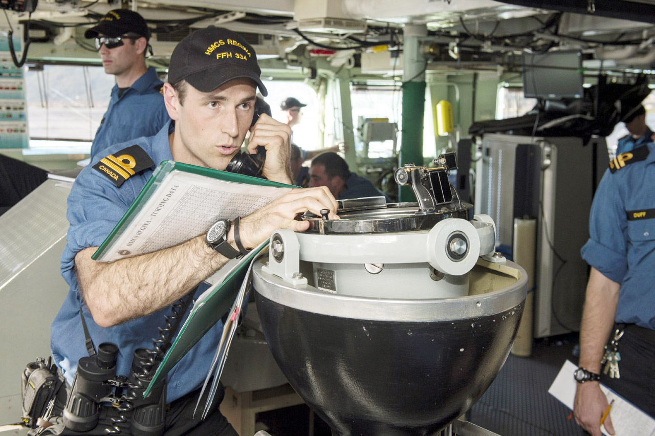 Lieutenant (Navy) Markian Haluszka, HMCS Regina's navigating officer, takes a bearing on the bridge.