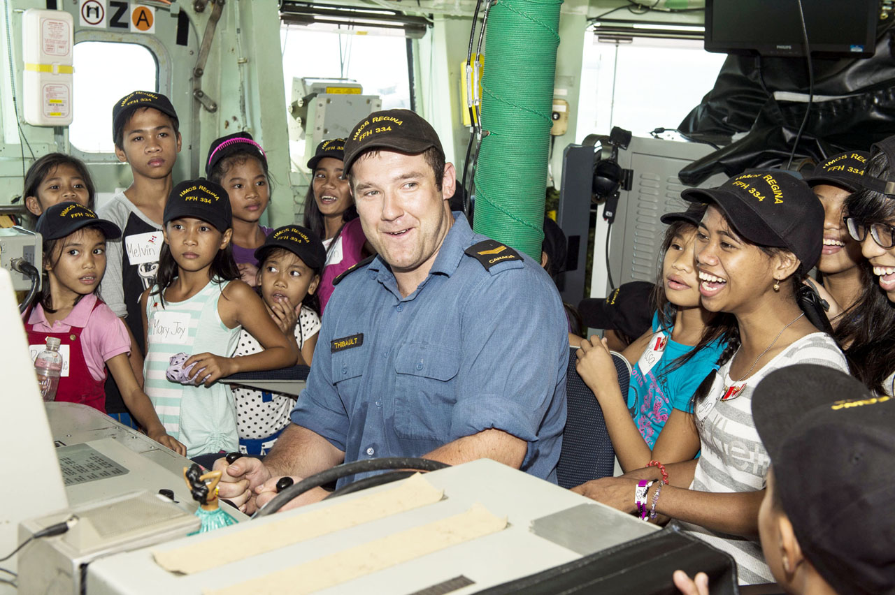 Leading Seaman Lee Thibault shows local children how to use the ship's helm as they visit HMCS Regina in Manila, Philippines.
