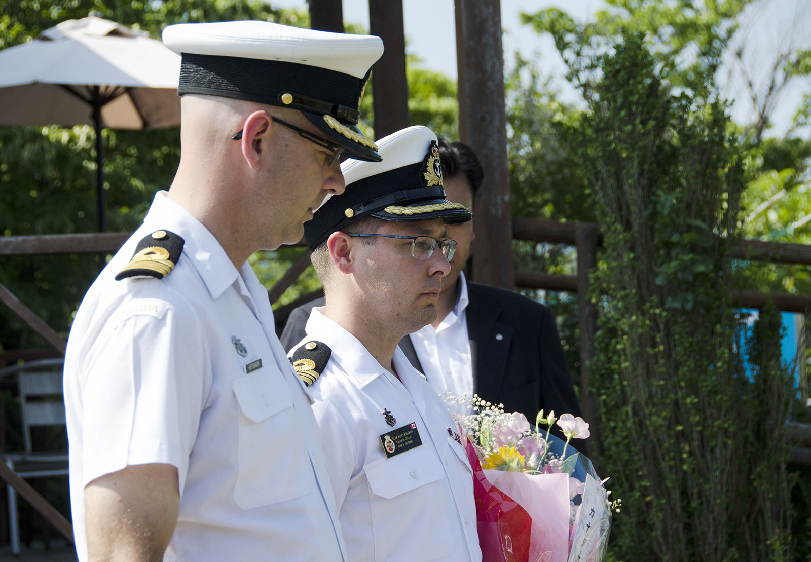 Commander Jeff Hutchinson, Commanding Officer, HMCS Winnipeg, and Lieutenant-Commander Scott Kelemen, Executive Officer, HMCS Ottawa, lay flowers at a memorial for the victims of the 2011 Tohoku earthquake and tsunami.