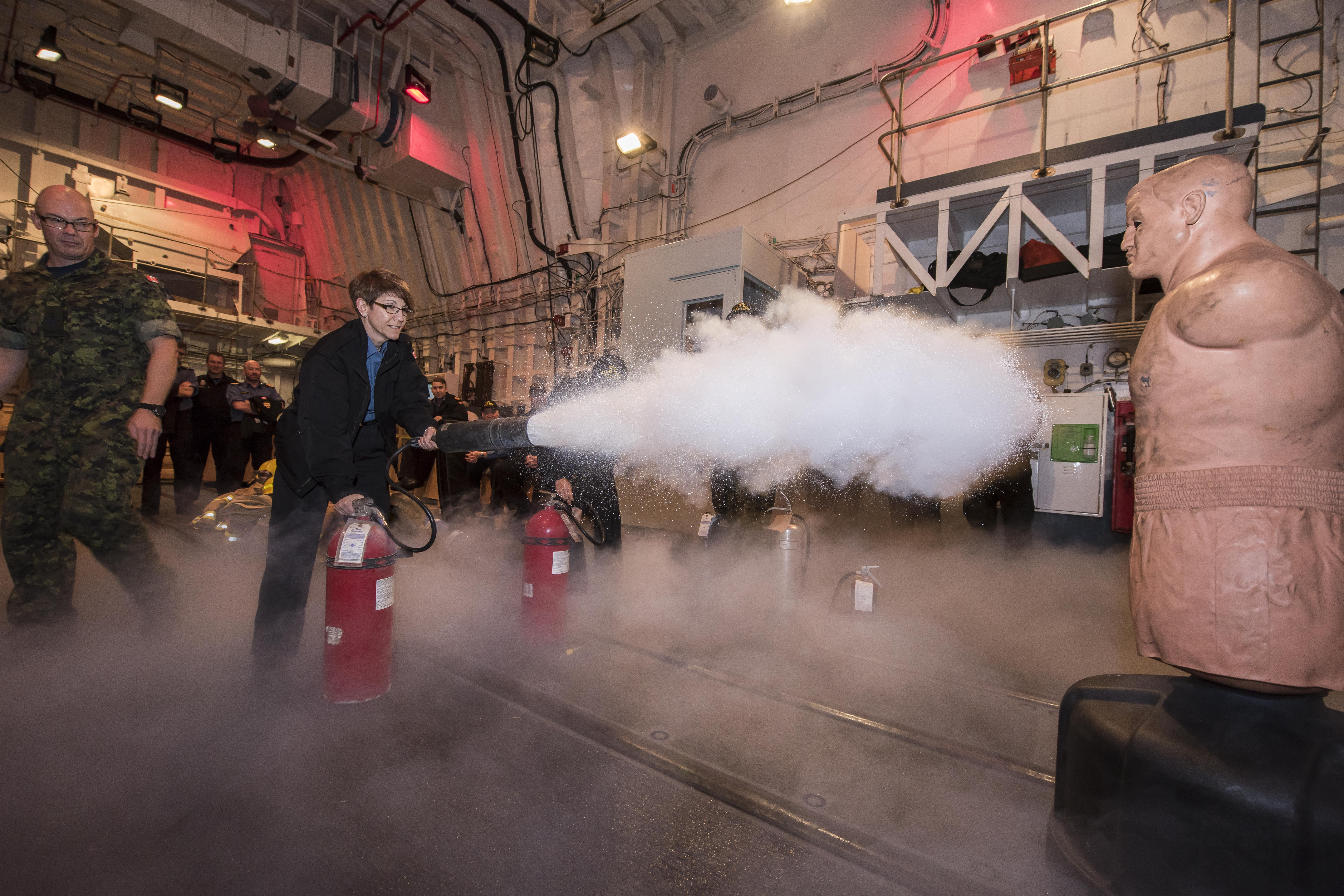 Member of Parliament Kelly Block gives a fire extinguisher a try during a damage control presentation in the hangar, before heading out to the flight deck in full fire gear to receive fire hose training.