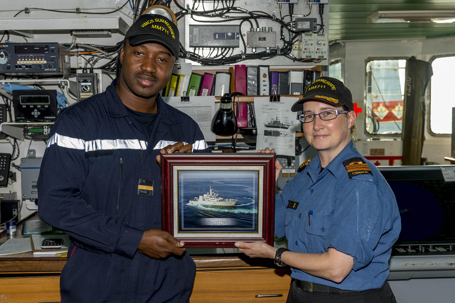 slide - Sub-Lieutenant Lassina Traoré, left, a member of the Ivory Coast Navy, receives a framed photograph of HMCS Summerside from Commanding Officer Lieutenant-Commander Emily Lambert, to remind him of his time as an exchange officer aboard the ship.