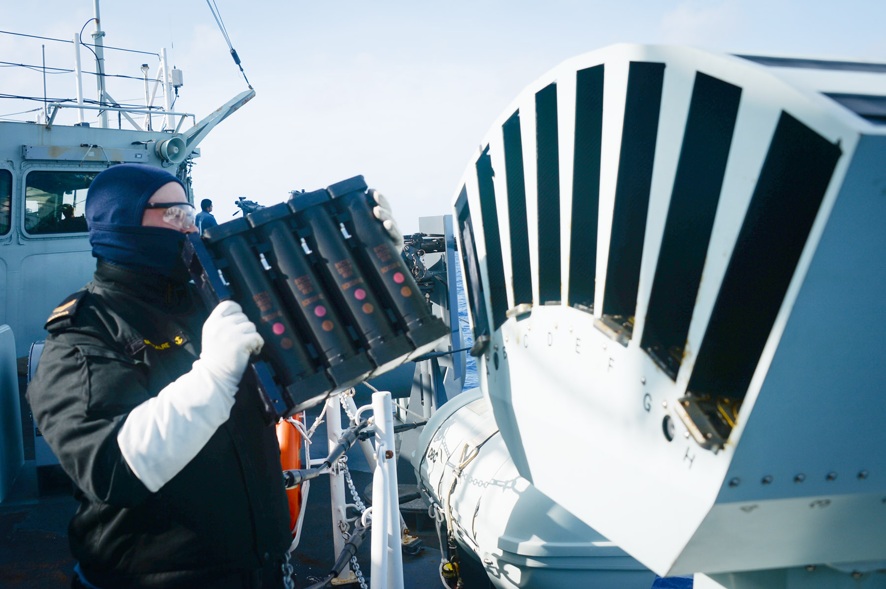 A sailor onboard HMCS Vancouver loads the Multi-Ammo Soft Kill System during RIMPAC.