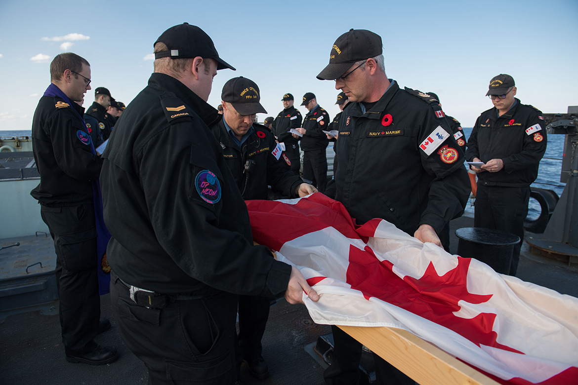 Members of HMCS Ottawa lay the Canadian Flag over the ashes of seven veterans.