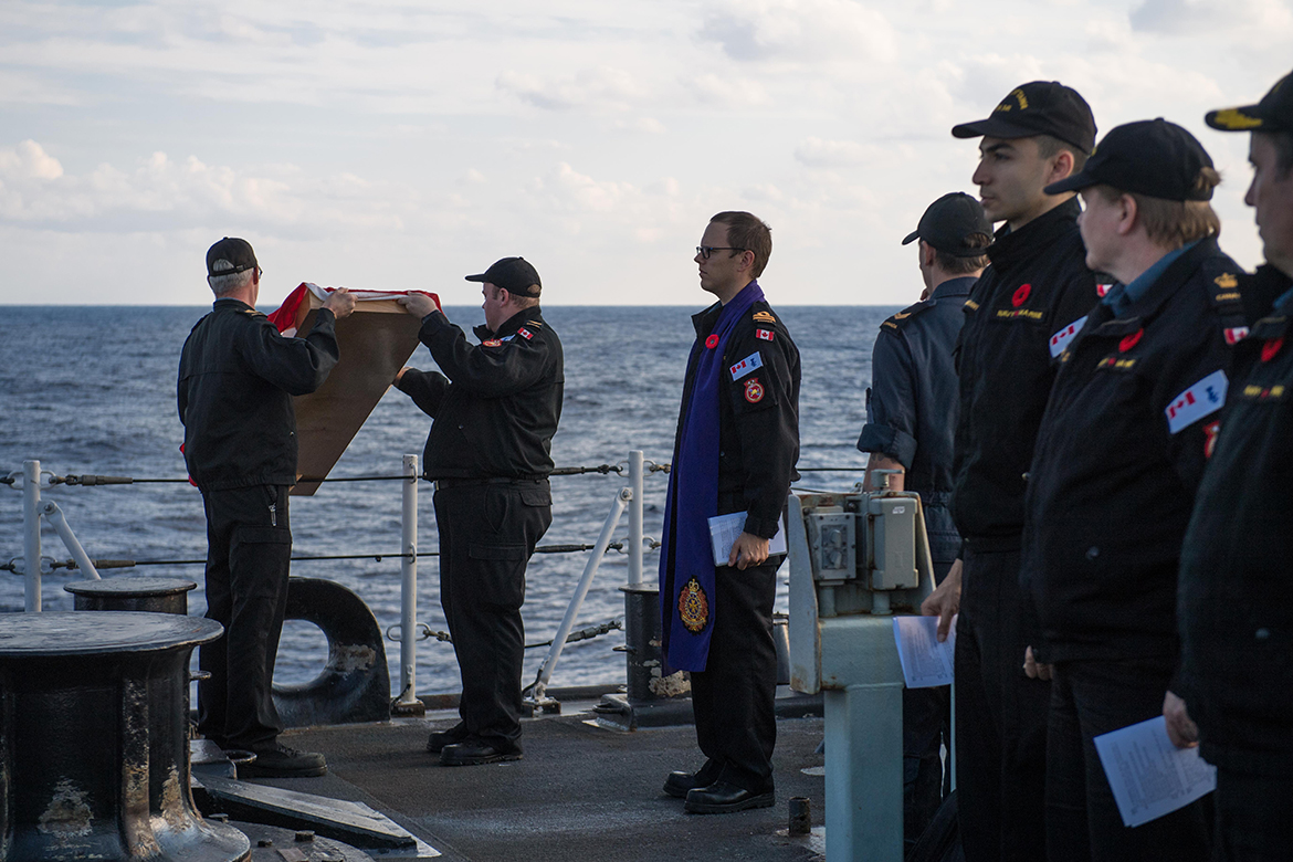 Members of HMCS Ottawa committing a veteran's ashes to sea during a ceremony on November 10, 2019.
