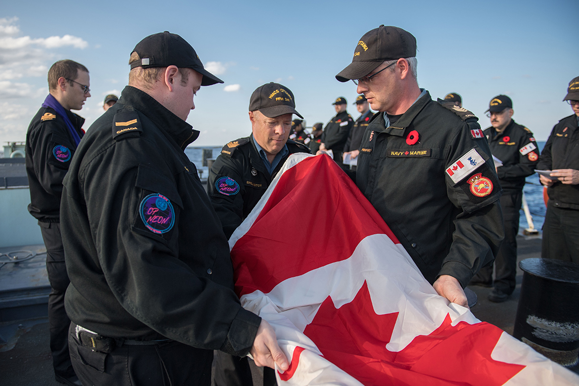 Members of HMCS Ottawa lay the Canadian Flag over the ashes of seven veterans – two who served in the Second World War – during a Committal of Ashes to Sea ceremony on November 10, 2019.