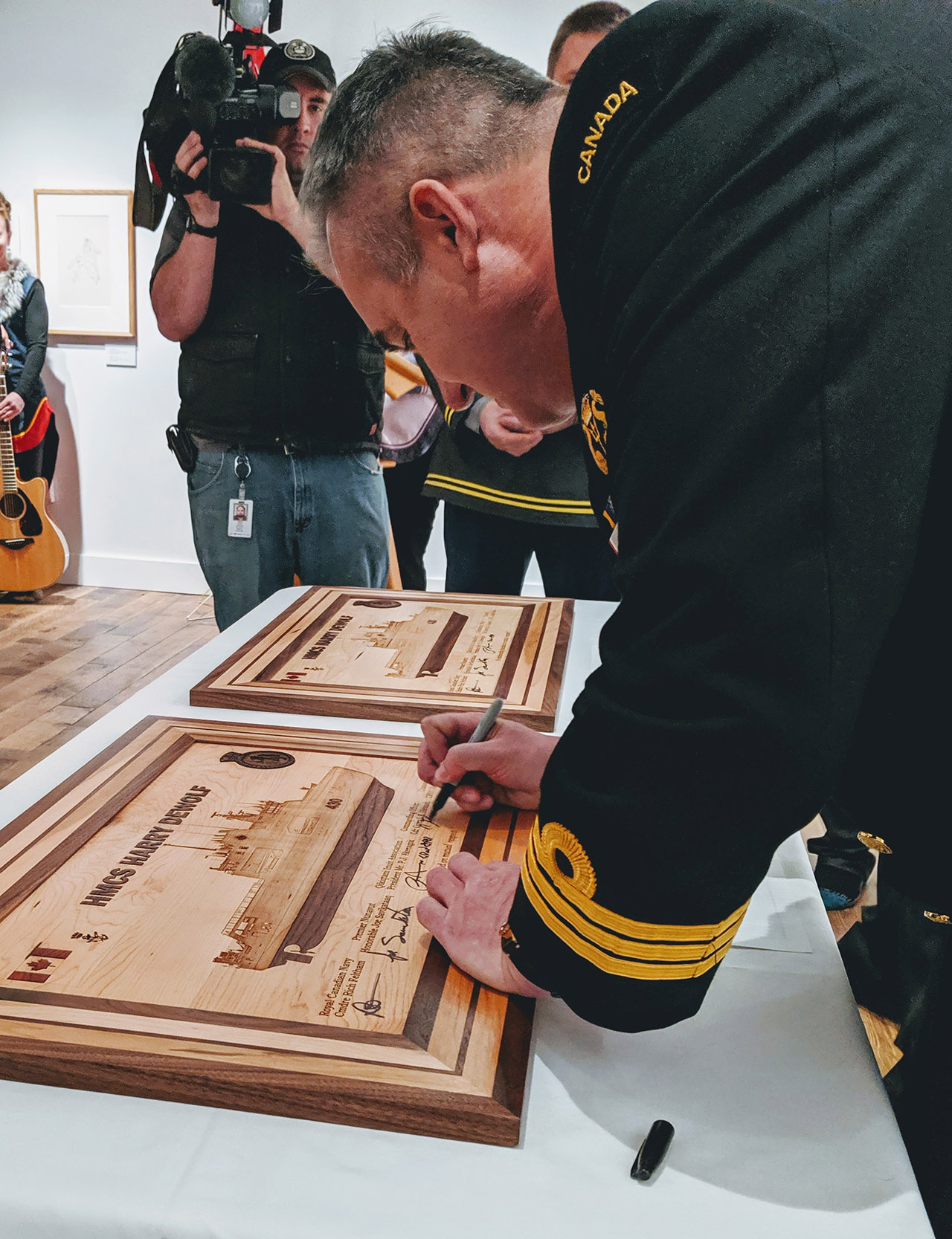 Commanding Officer, Commander Corey Gleason signing ceremonial plaques which formally recognize the affiliation of Her Majesty's Canadian Ship Harry DeWolf and the Qikiqtani region of Nunavut.