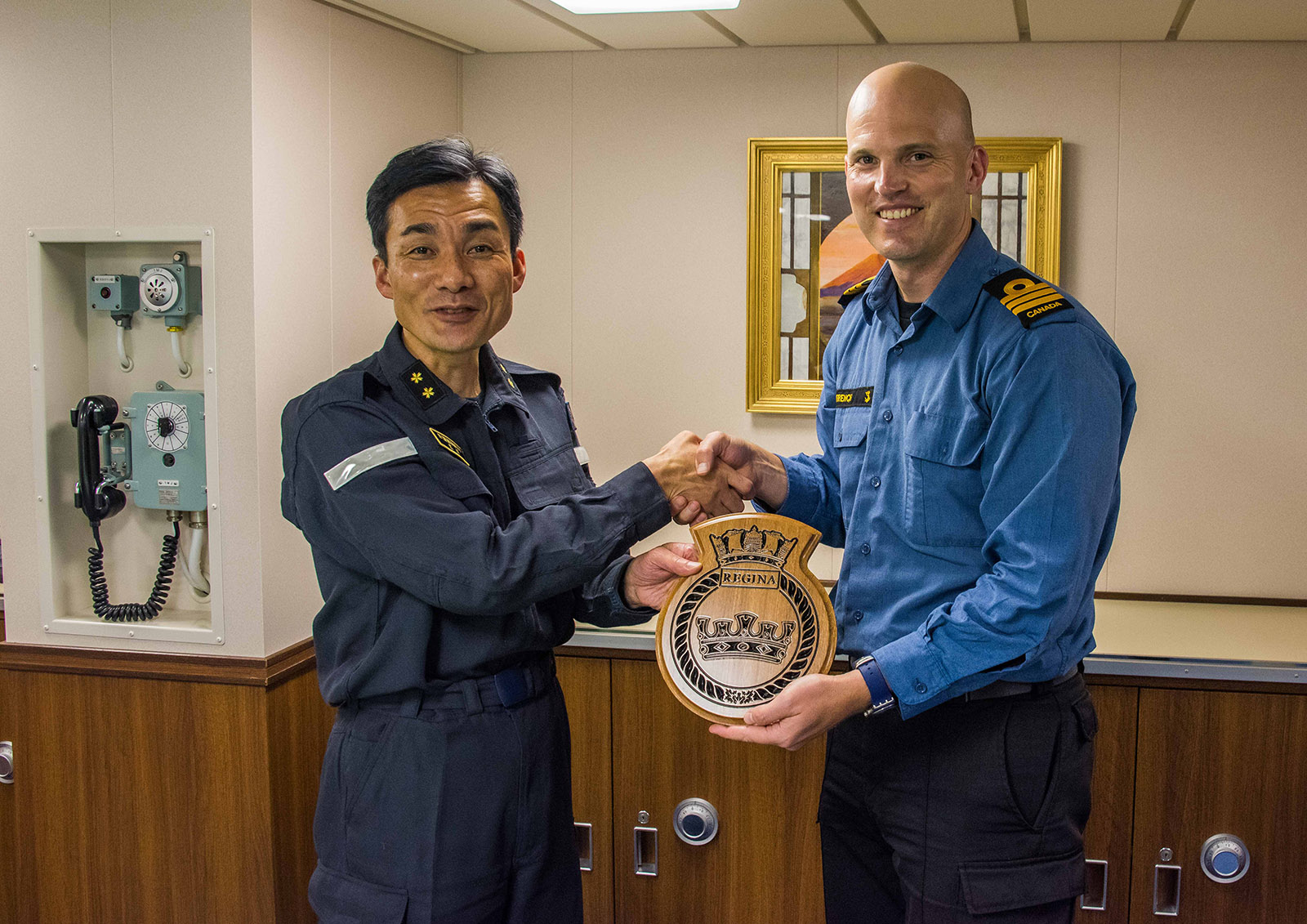 HMCS Regina's Commanding Officer, Commander Jacob French, right, presents a commemorative gift to the Commanding Officer of JS Akebono.