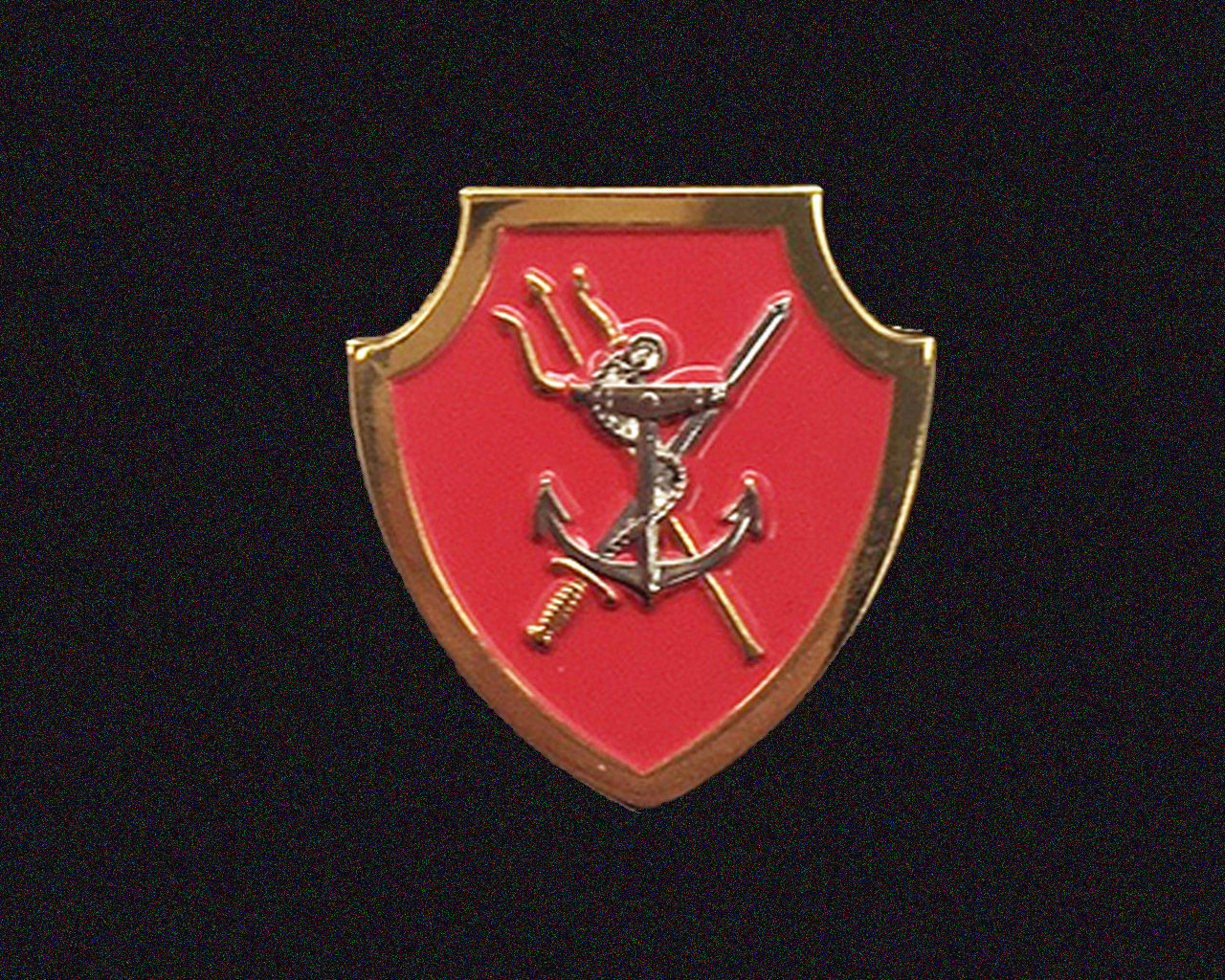 The NSTQ badge is a red shield bordered by gold trim 3 cm in height. A gold trident is crossed with a naval cutlass with a silver fouled anchor in the foreground.