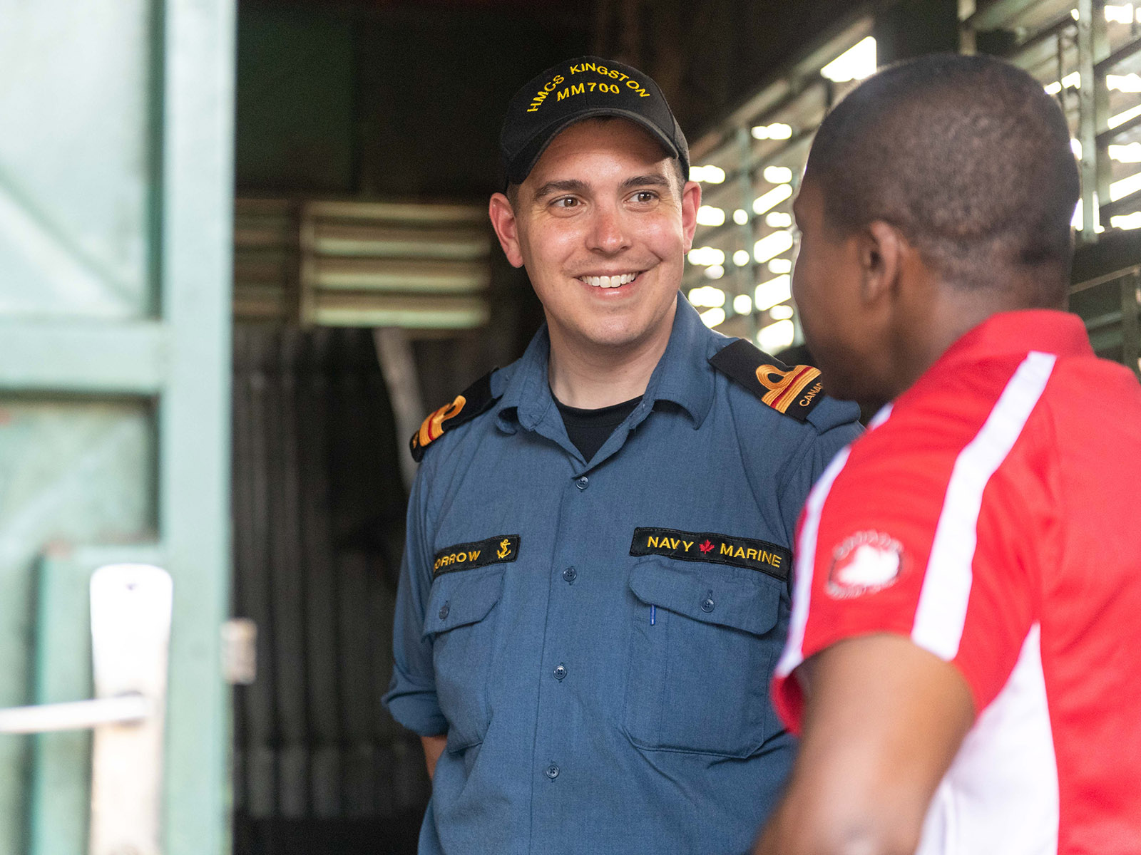 Lt(N) Greg Morrow chats with Canada's Ambassador to Benin, Edmond Wega, at Foyer Don Bosco school in Cotonou, Benin after providing first aid training during Operation PROJECTION West Africa on March 1, 2019.