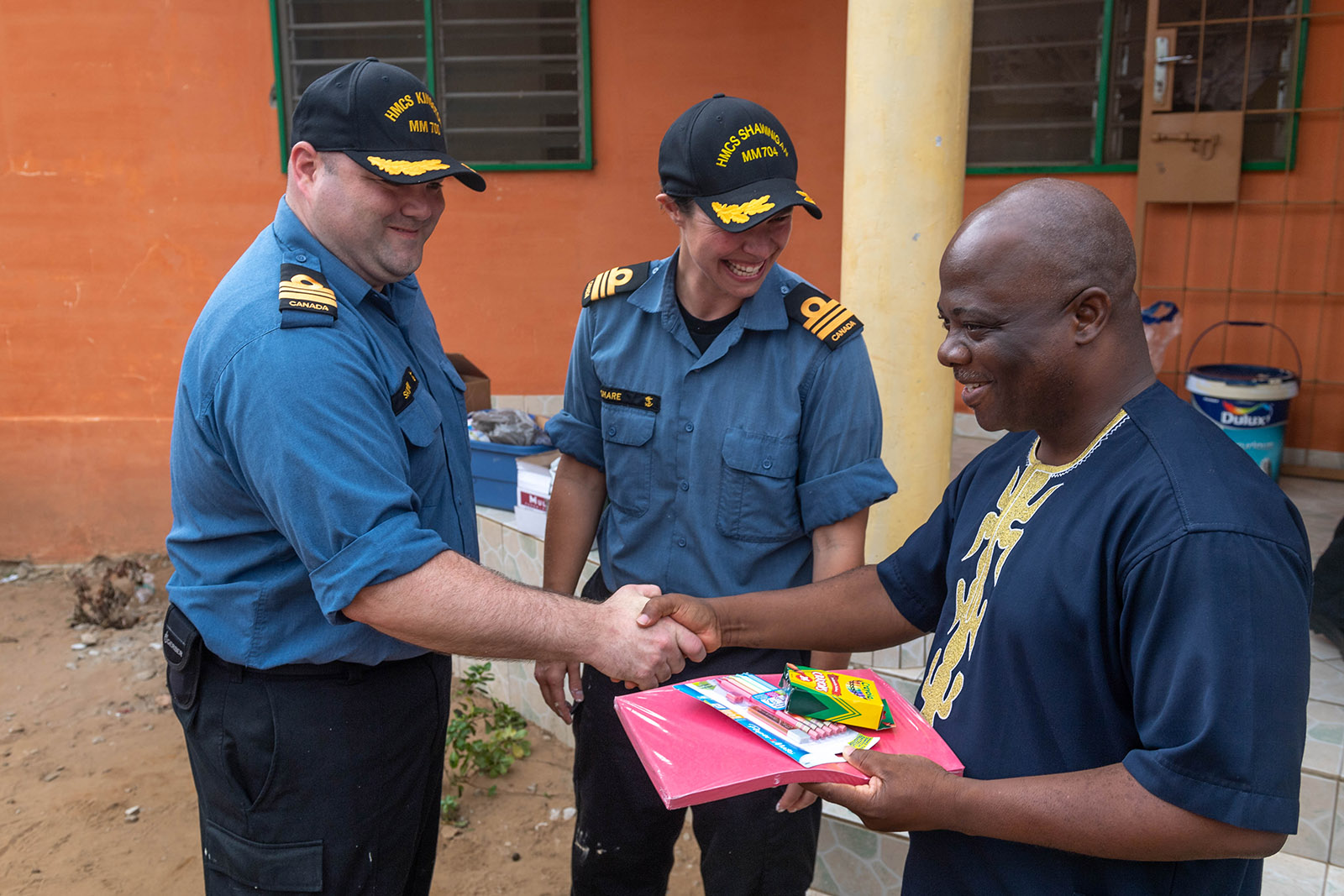 The Commanding Officers of HMCS Shawinigan and Kingston present donated school supplies to the director of L'Espace de Fraternité in Lomé, Togo on March 6, 2019.