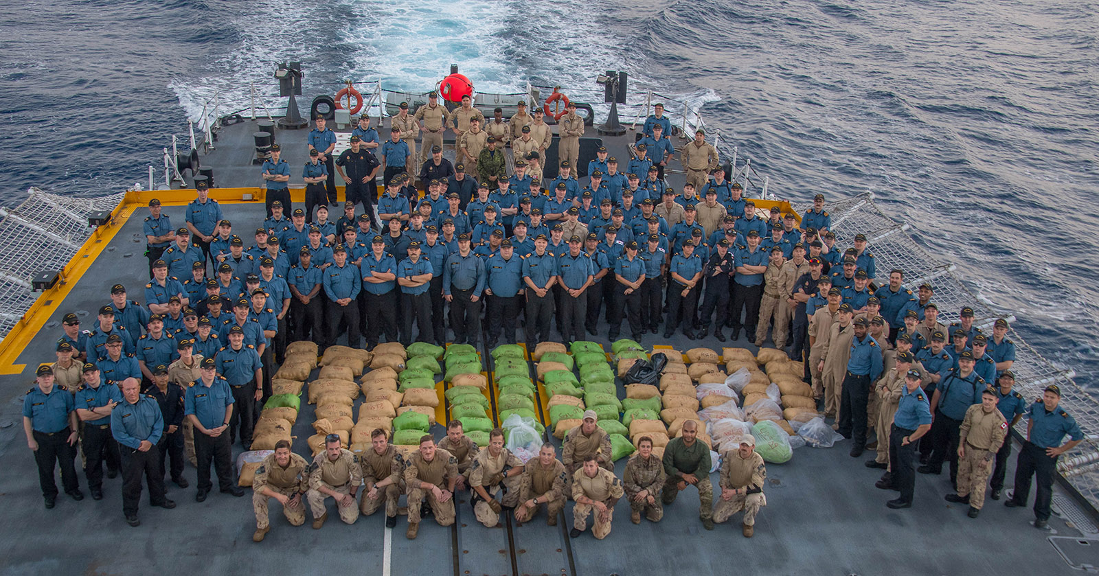 HMCS REGINA's crew poses with over 2000 kilograms of narcotics seized from a dhow during Operation ARTEMIS in the Pacific Ocean on April 7 2019.