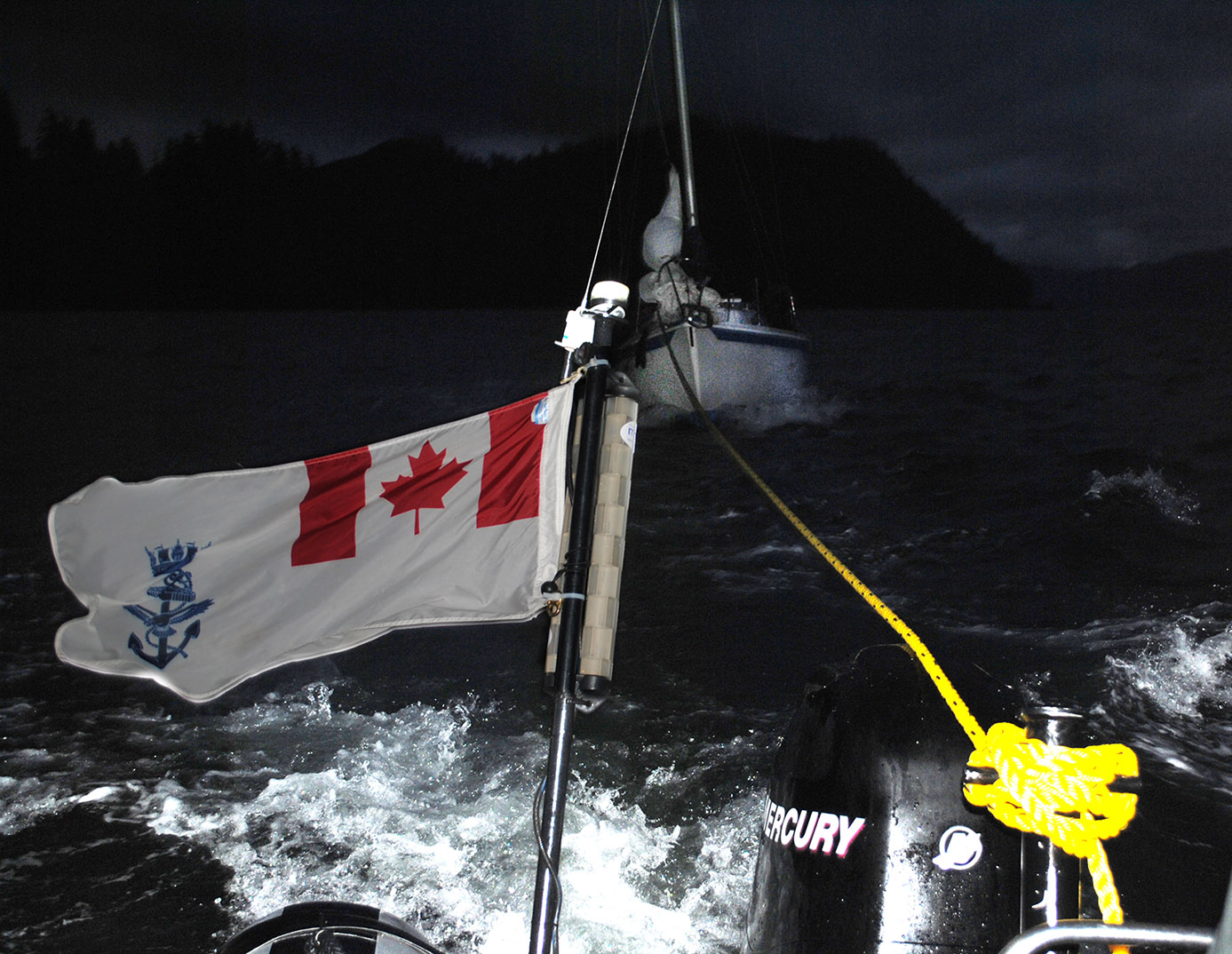 HMCS Whitehorse's rigid-hulled inflatable boat tows a sailboat through rough seas into Winter Harbour, B.C., after receiving a distress signal on August 16. (The lighting of this photo has been adjusted to make the sailboat more visible.)