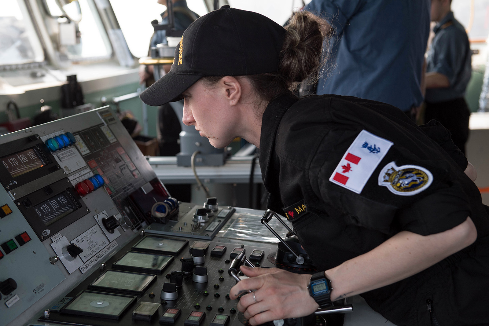 A member of the Royal Canadian Navy acts as the helmsman during departure to Op CARIBBE 2020, at a foreign port, on February 18, 2020.