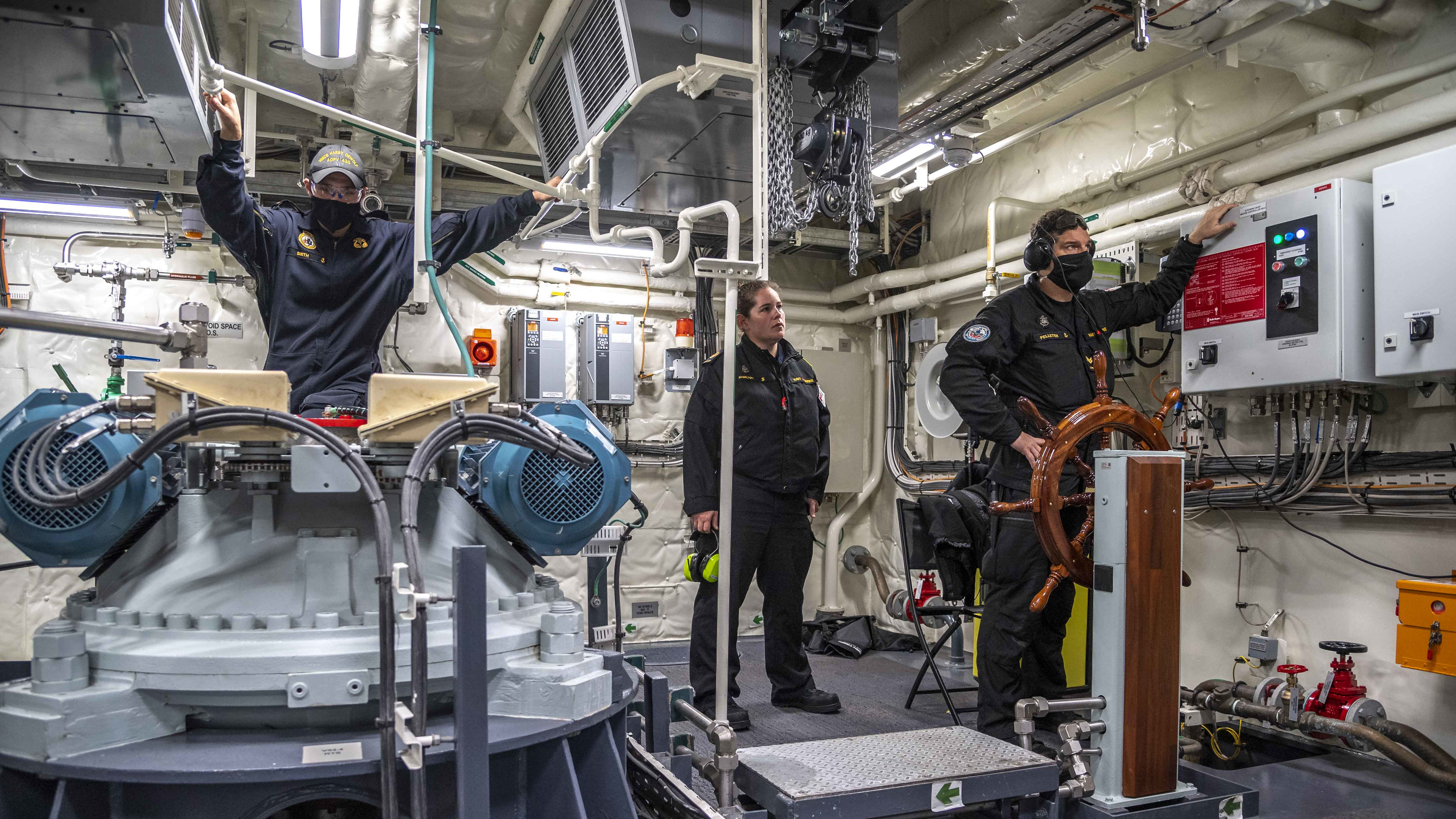 Sailor 1st Class (S1) Smith, Petty Officer 2nd Class Hamilton and S1 Pelletier conduct an emergency steering drill aboard HMCS Harry DeWolf on November 13.