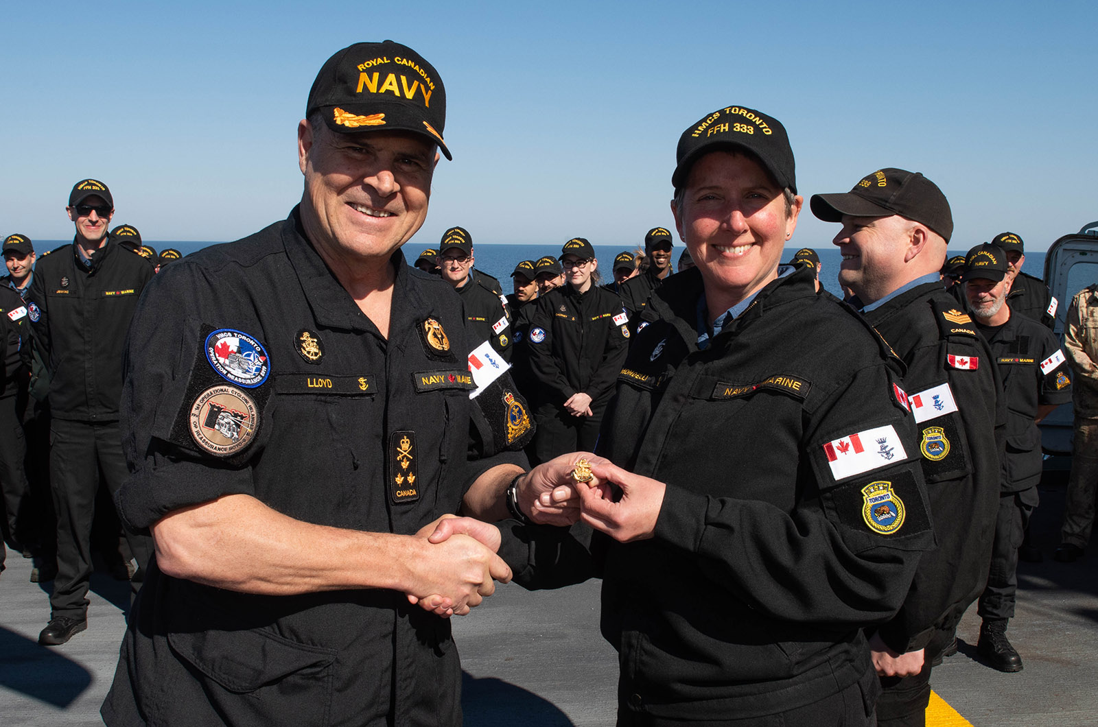 Vice-Admiral (retired) Ron Lloyd, former Commander Royal Canadian Navy (left) presents Chief Petty Officer 1st Class Alena Mondelli, Coxswain of HMCS Toronto, with the Sea Service Insignia – Gold awarded for 1460 days at sea, on the flight deck while deployed in the Black Sea during Operation REASSURANCE ROTO 10, April 4, 2019.
