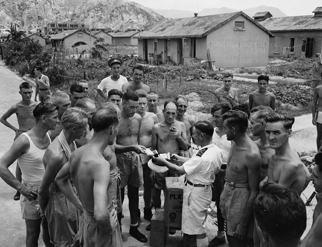 Lieutenant-Commander Fred Day and officers of the auxiliary anti-aircraft ship HMCS Prince Robert with liberated Canadian prisoners-of-war at Shamshuipo Camp, Hong Kong, August 1945.