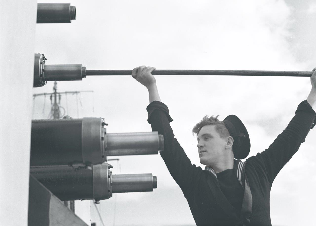 Crew member cleans one of HMCS Prince Robert's Oerlikon guns.