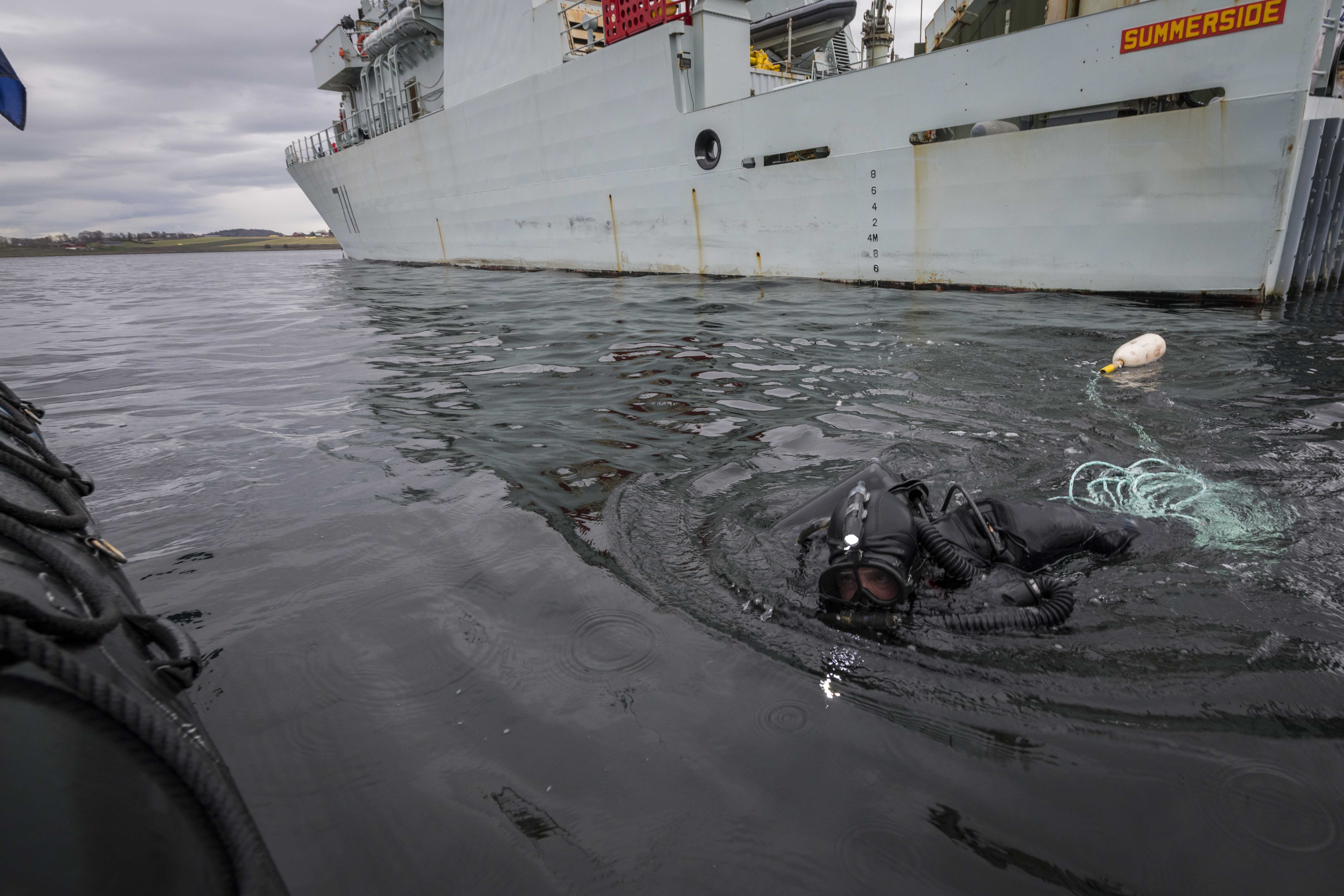A Royal Canadian Navy clearance diver inspects under Her Majesty's Canadian Ship (HMCS) Summerside during Exercise TRIDENT JUNCTURE, in the fjords of Norway, in 2018.