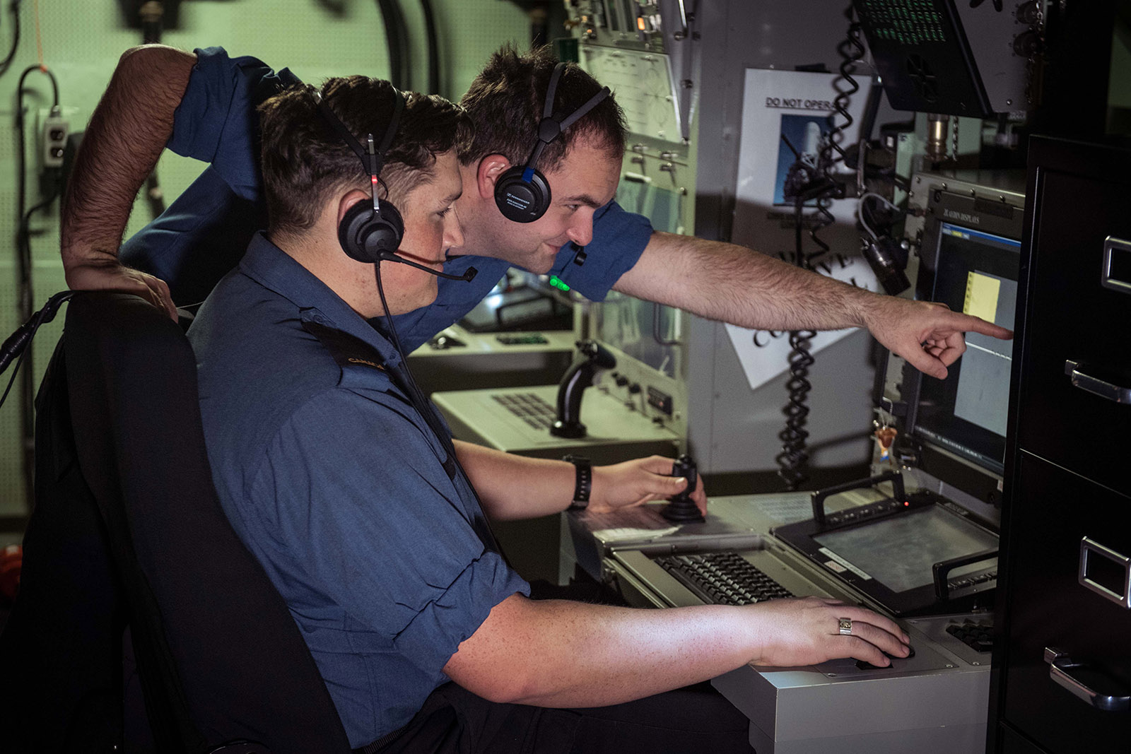 MS Firat Ataman, Forward Fire Control Supervisor mentors OS Walker Grant as he becomes familiar with the Forward Fire Control Radar Console onboard HMCS OTTAWA during Operation PROJECTION.