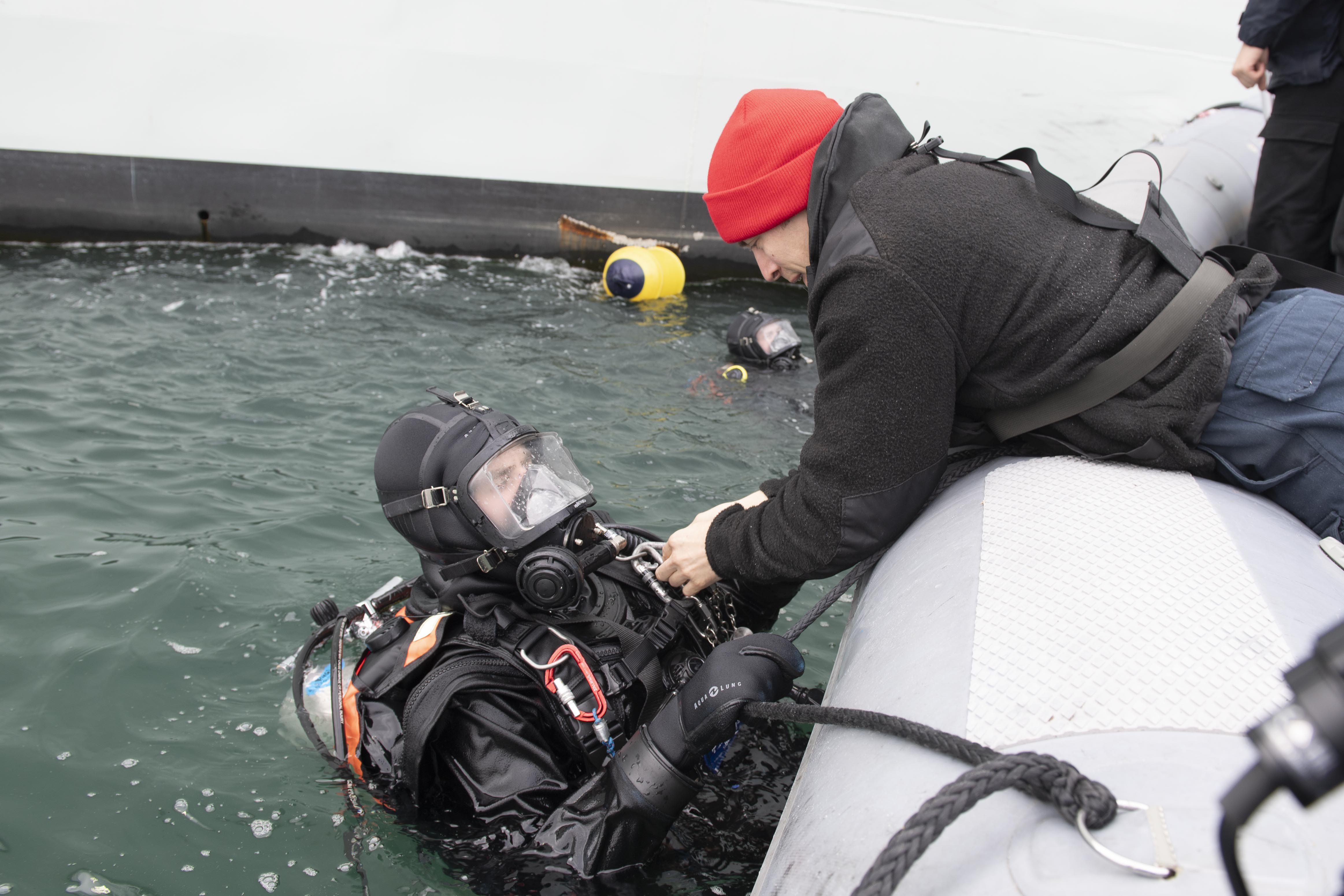 Leading Seaman (LS) Cory Taylor (right) helps LS John Kester to remove his gear at the conclusion of a diving operation at the Port of Reykjavik, Iceland
