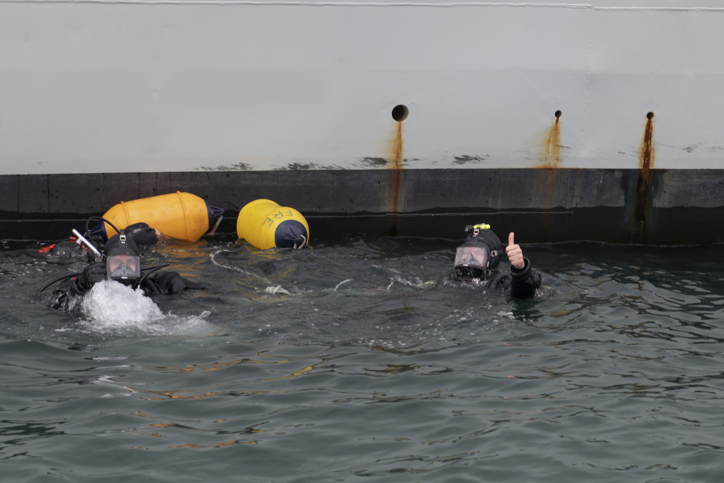 Leading Seaman John Kester (left) and Lieutenant (Navy) Sebastien Williamson give a thumbs up during a routine inspection of HMCS Fredericton at the Port of Reykjavik, Iceland during Operation REASSURANCE, in July 2020. The RCN rank of leading seaman has since been changed to sailor 1st class.